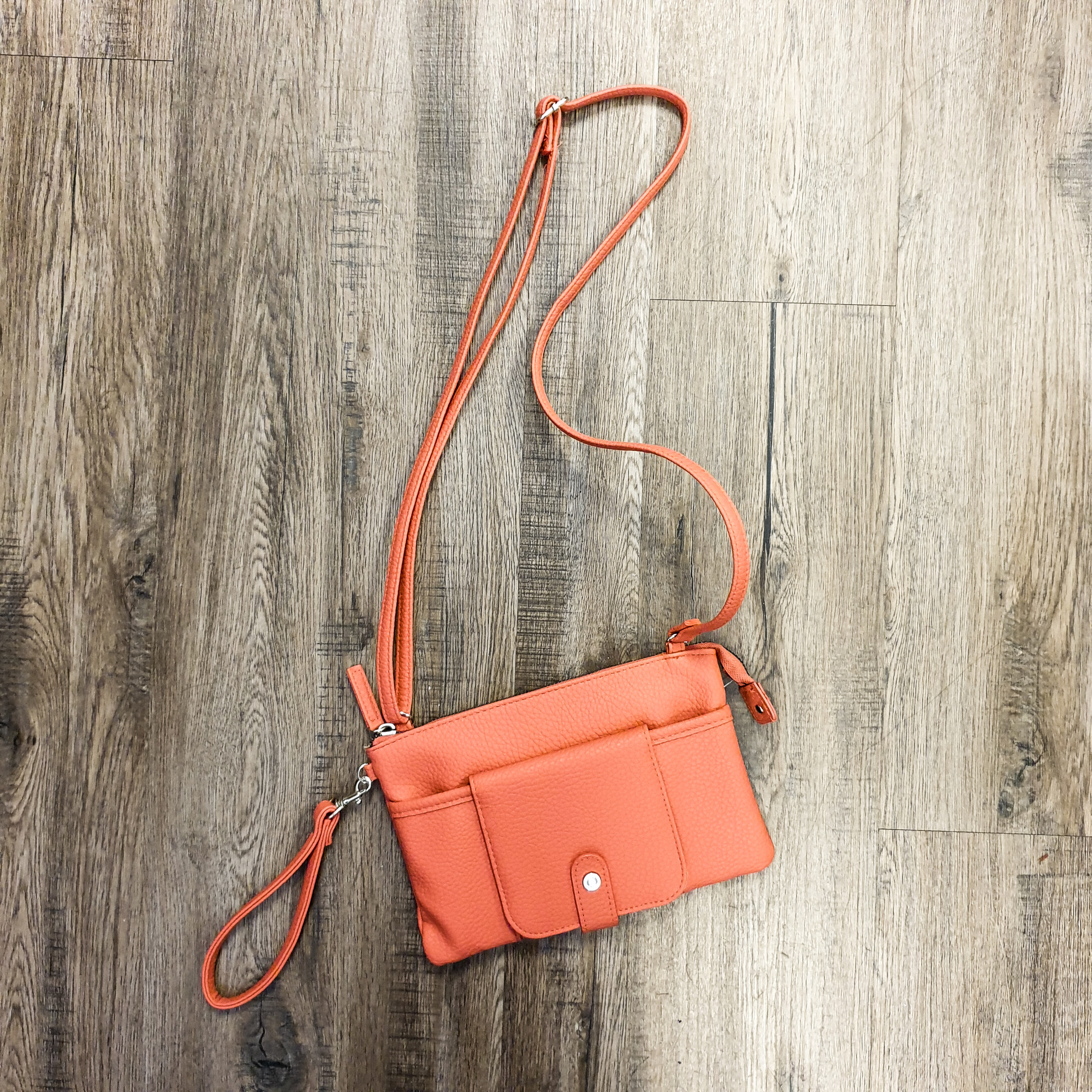 Beautiful Crossbody.<br /> - Coral color<br /> - Zip-top closure<br /> - Front slip pocket with ID window, two card slips and one zip pocket<br /> - Adjustable shoulder strap with 25 in. drop<br /> - Removable wristlet<br /> - Interior features: one slip pocket<br /> - W: 8.5 in. H: 6 in. D: 1 in.<br /> <br /> * Please note that these measurements and pictures are for reference only and may vary slightly from the original.