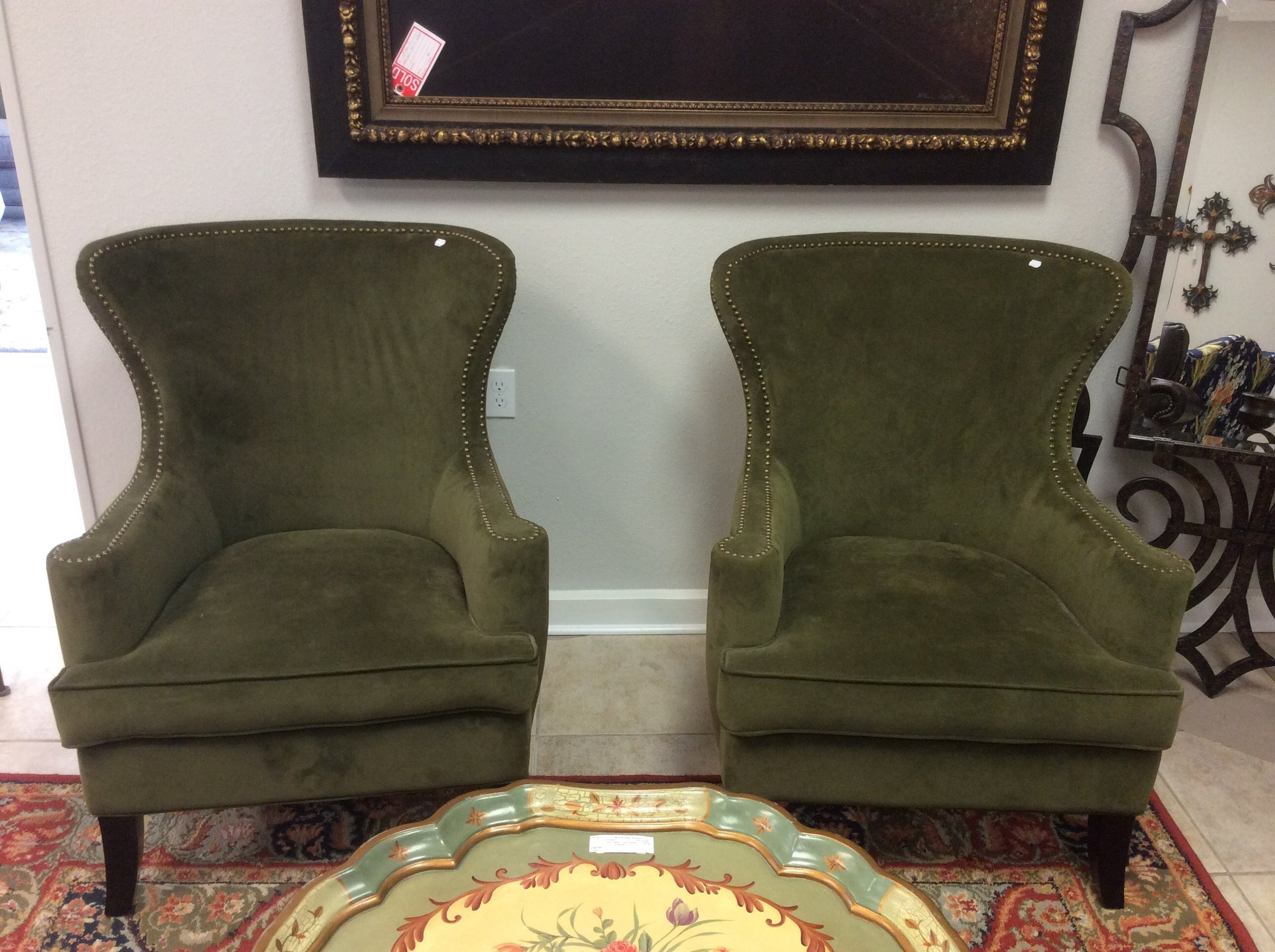 This duo features a quasi-wingback style. The cushions are not removable and there are brass nailhead accents along the arms and up around the back.