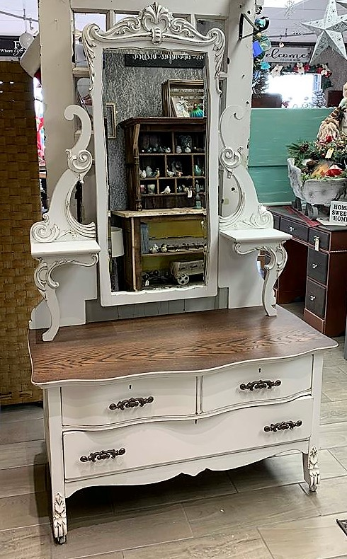 Antique Dresser With Mirror<br /> Beautiful antique washstand style dresser with oversized mirror. It has unique ornate detailings on the legs of the dresser and the around the mirror. It includes two small shelves that attach to the mirror frame. the entire piece has been painted a bright white with distressing. The top has been stained walnut for a natural look that ties in the distressing on the rest of the piece. Dresser measures 45&quot; wide x 21&quot; deep x 76&quot; tall (dresser is 25&quot;, mirror is 51&quot;). Buzz on in today!