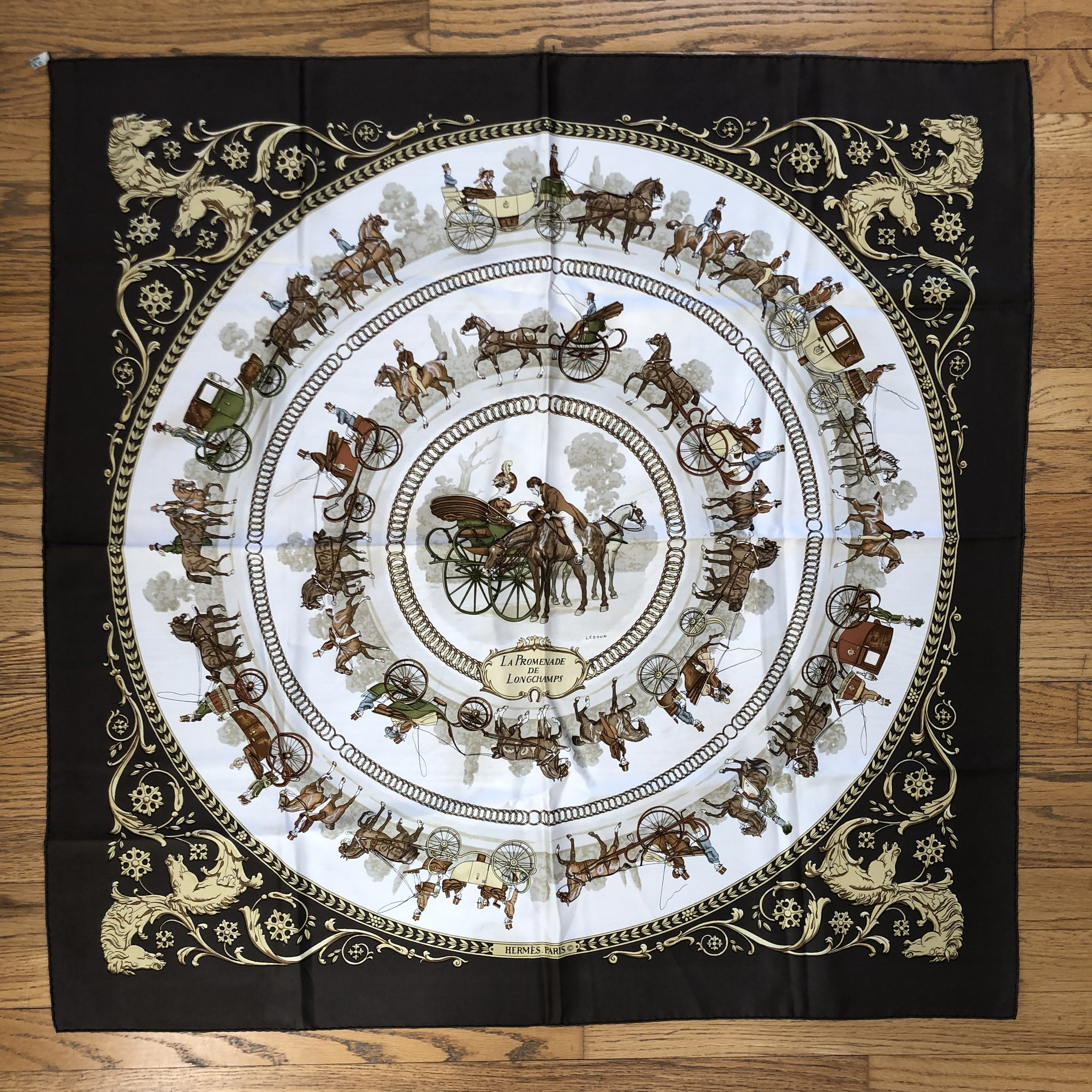 A lovely, pre-loved Vintage HERMES Scarf<br /> Design: Promenade De Longchamps<br /> Colors: Browns, Cream, Green, Gold<br /> Size: 45&quot; x 45&quot; (approximate dimensions, which will vary due to wear and cleaning)<br /> Condition: No tears. There are smudges/spots which appear as light brown.<br /> This is a pre-loved scarf, sold in &quot;AS IS&quot; condition. Please see the last pictures for examples of the light brown smudges/spots.