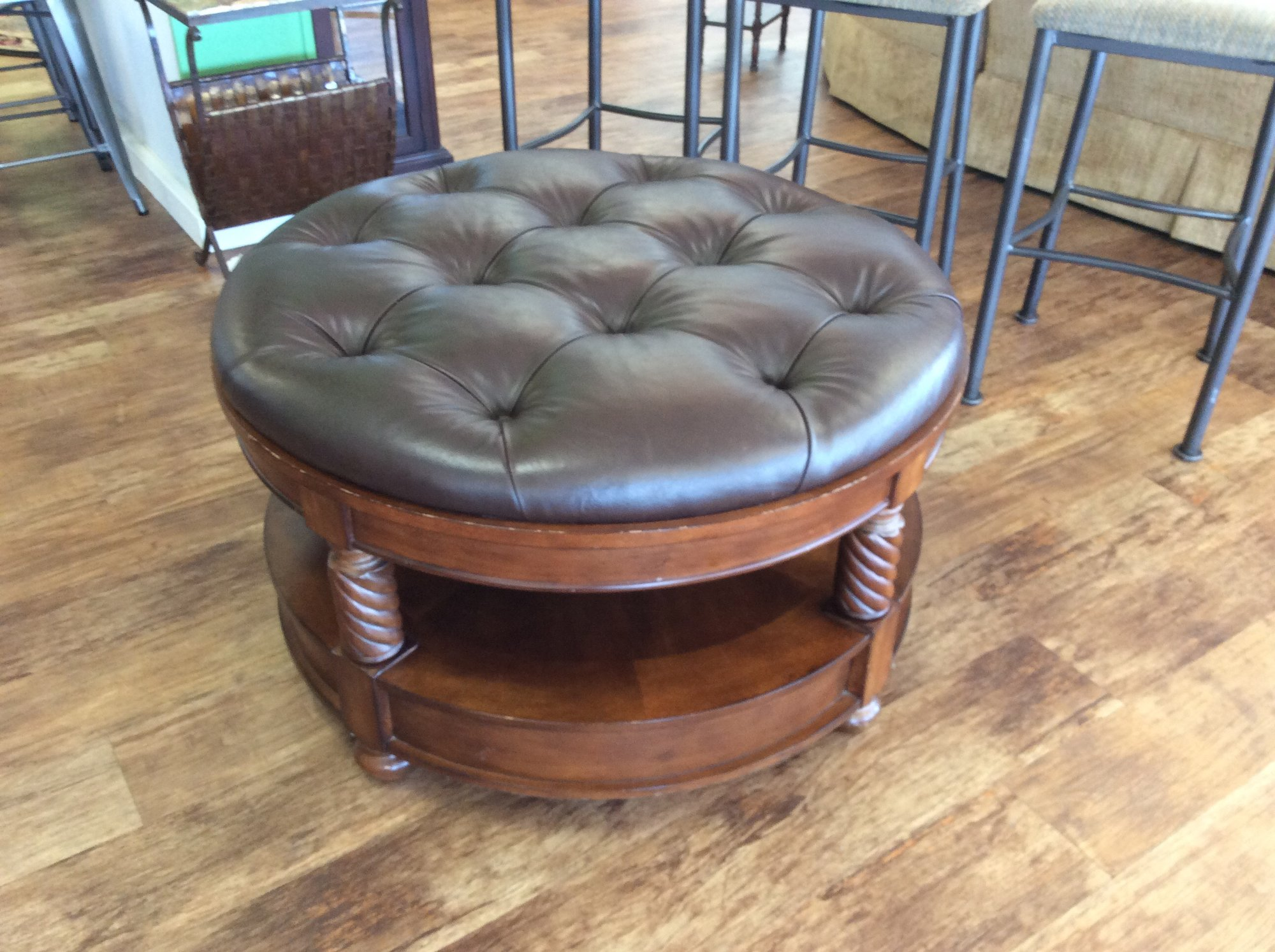 This handsome ottoman features a solid wood base with a cherry finish. There is single drawer at the bottom and a pull out tray near the top. The brown leather top is tufted, as well.