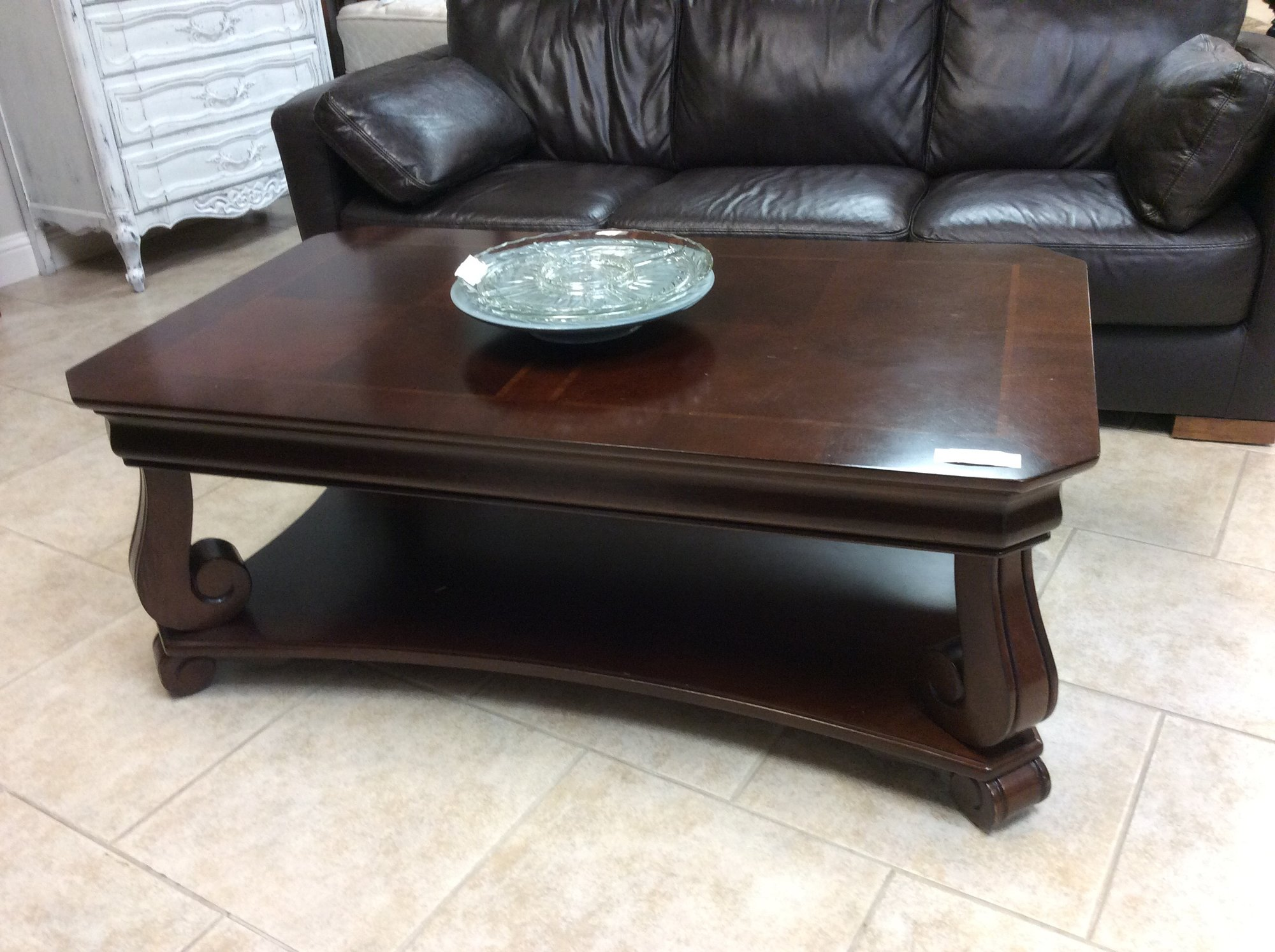 This handsome coffee table appears to be solid wood. It has a mahogany finish, as well as pretty inlaid wood designs on the top.