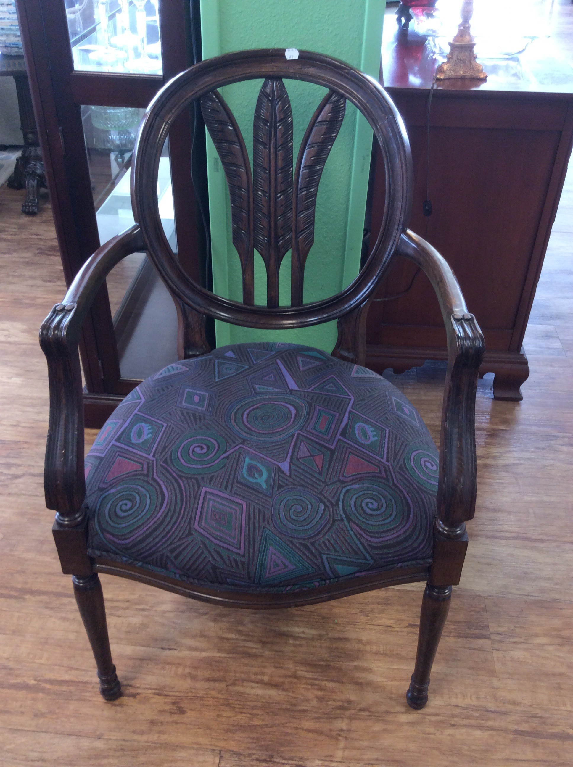 This is an interesting arm chair! It features a lovely carved wood frame in a rich, dark finish. The seat is upholstered in a thoroughly modern geometric pattern of purples, greens, black and pinky/red. Come by and take a look soon!