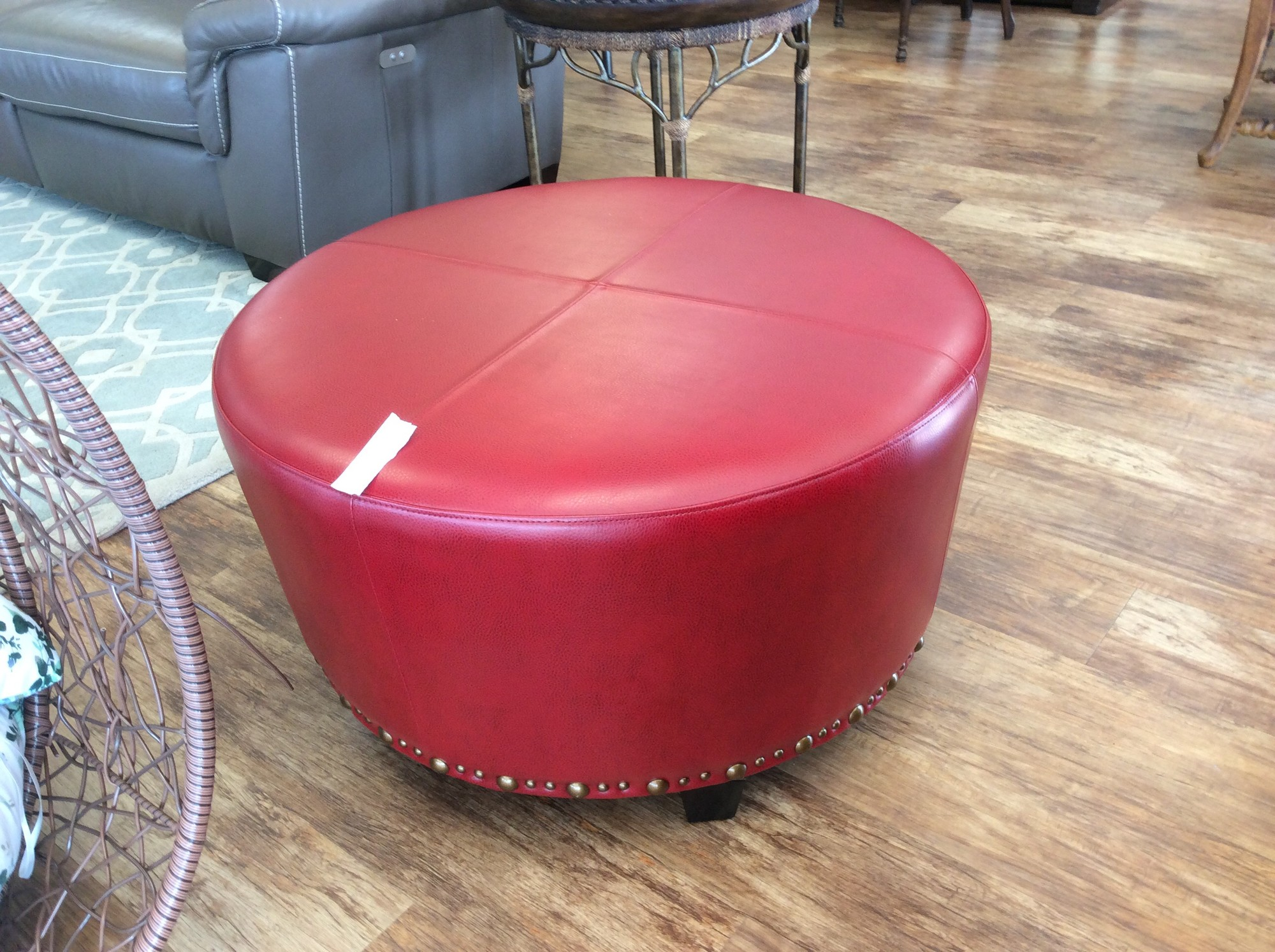 Well, now, isn't this cute! If you have a room in need of a slash of color, perhaps this piece is for you. It features pretty red pleather upholstery, as well as 2 sizes of bronze nailhead accents around the bottom.