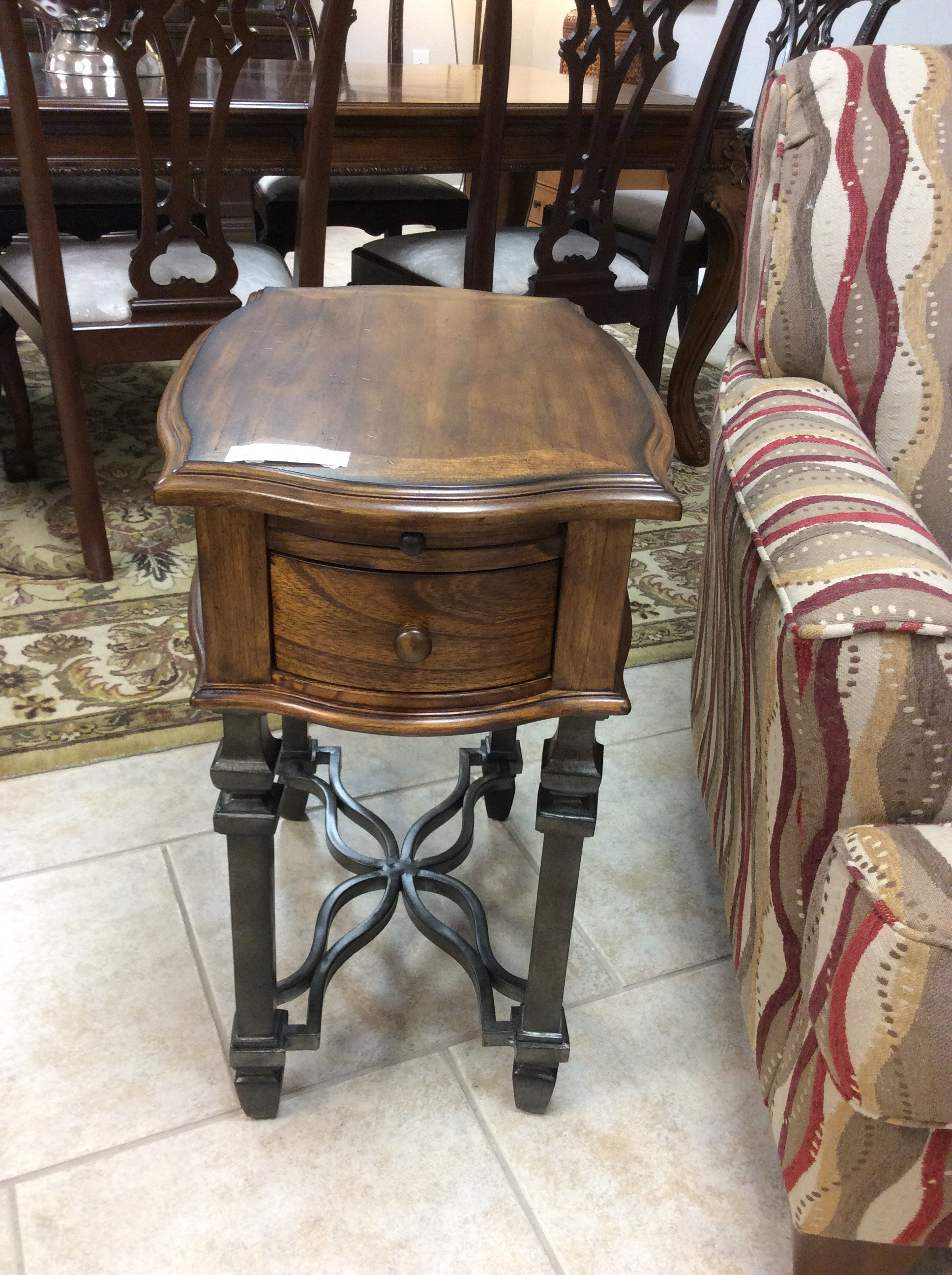 This is a really smart looking side table. The solid iron base has a pretty, gun metal gray finish. The solid wood top is shaped like a quatrafoil and has both a pull out drink tray, and a single drawer. There is also a matching larger side table that is available for purchase seperately.