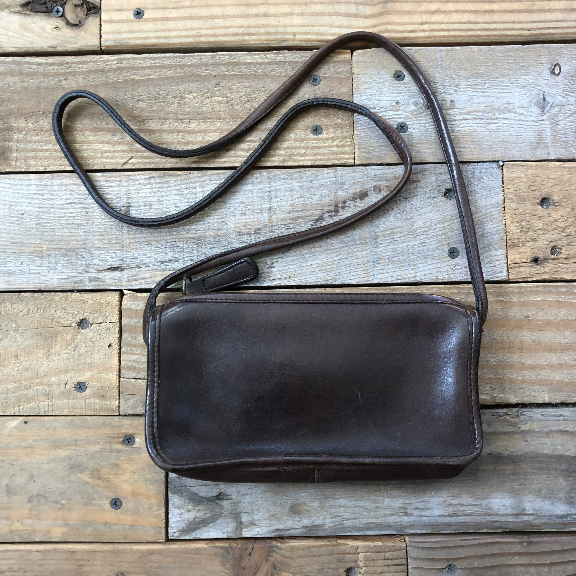 "Vintage Coach Leather Crossbody Bag<br /> Color: Brown<br /> Size: 9"" x 5"" x 2""<br /> <br /> Features:<br /> -zippered closure<br /> -21"" crossbody strap<br /> -interior pocket<br /> *shows signs of wear from age (surface scratches on leather)"