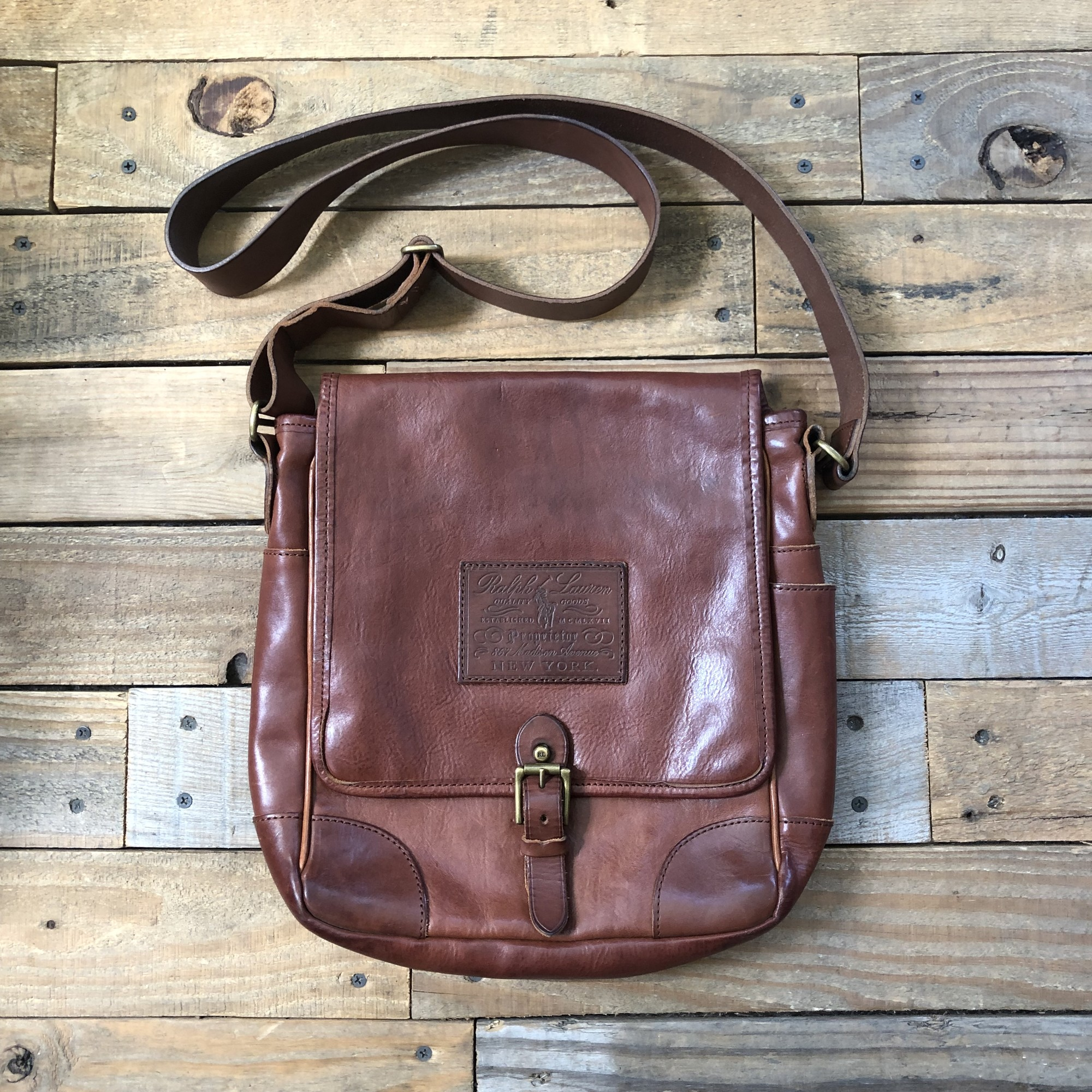 "Ralph Lauren Leather Messenger Bag<br /> Color: Brown<br /> Size: 10"" x 11"" x 2.5""<br /> <br /> Features:<br /> -flap with buckle closure<br /> -adjustable leather crossbody/shoulder strap<br /> -exterior zippered pocket<br /> -interior zippered pocket<br /> -two interior pockets"