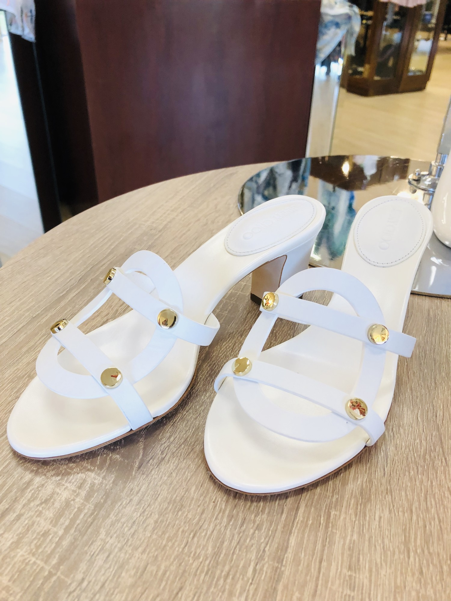 Jimmy Choo white Demaris sandals, gold stud embellishment. Size 38<br /> <br /> Small black mark on side of one shoe, see image