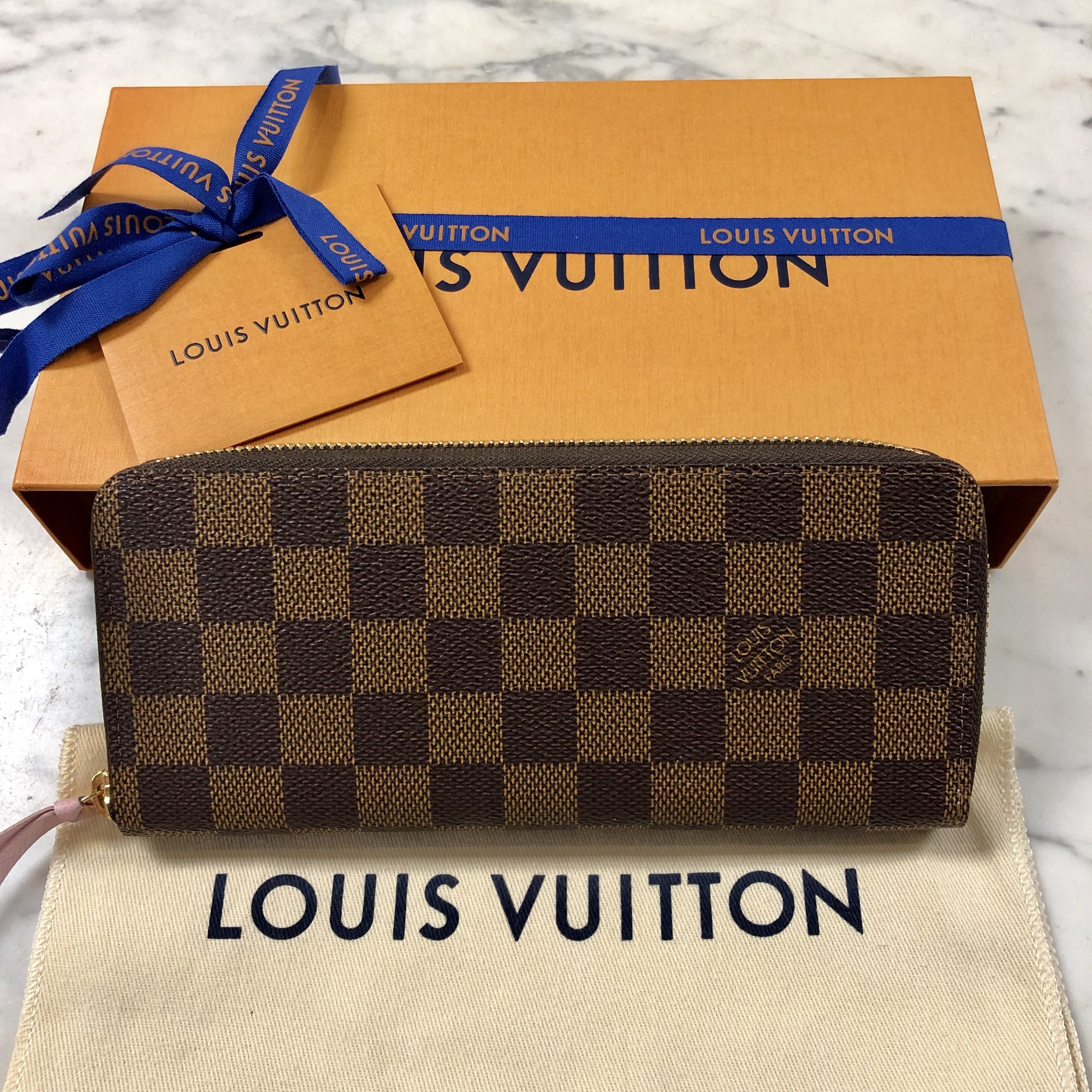 "Louis Vuitton Clements Wallet<br /> Compact yet with high capacity. Playful feminity is also part of its charm with its beautiful colored lining and leather zipper<br /> Color: Brown Checkered with Rose Ballerine (light pink) zipper pull and interior.<br /> Size: 7.7"" x 3.5"" x 0.6""<br /> Material: Coated Canvas, Grained Cowhide Leather lining and trim. New with tags, Box, Papers, Dust Cover.<br /> Gold color metal pieces.<br /> 8 Credit Card Slots<br /> 1 Zippered Coin Pocket<br /> 2 large Gussetted Compartments<br /> 2 Inside Flat Pockets<br /> 1 Leather Zipper"