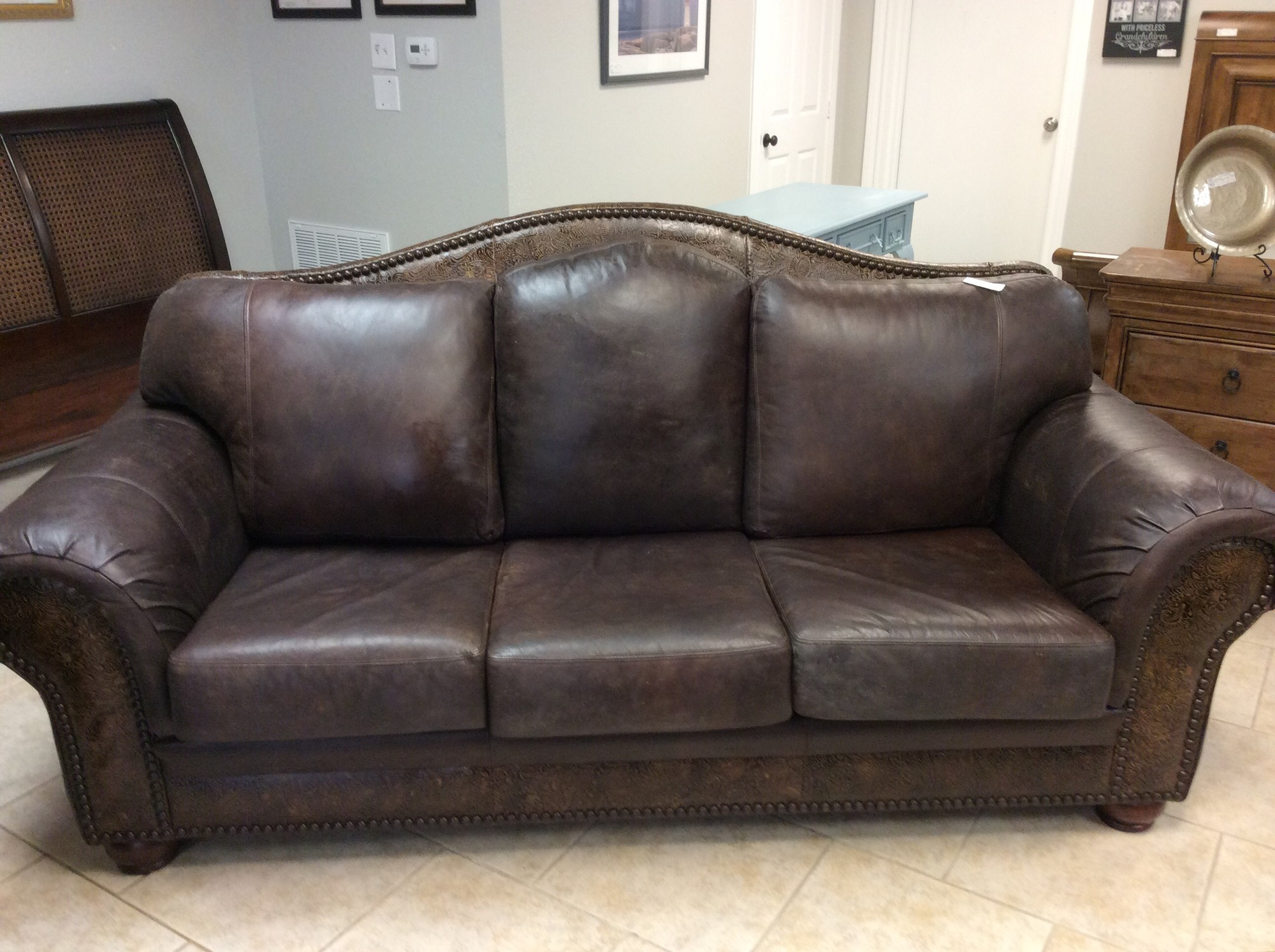 This handsome leather sofa is only 3 years old and came from GALLERY Furniture. The genuine leather upholstery is distressed for a rustic look. There are tooled leather panels across the back, the bottom front, and the fronts of the arms. All cushions are removable, but have sturdy velcro fasteners to minimize slippage. There is aslo a matching lovseat that is available for purchased seperately.