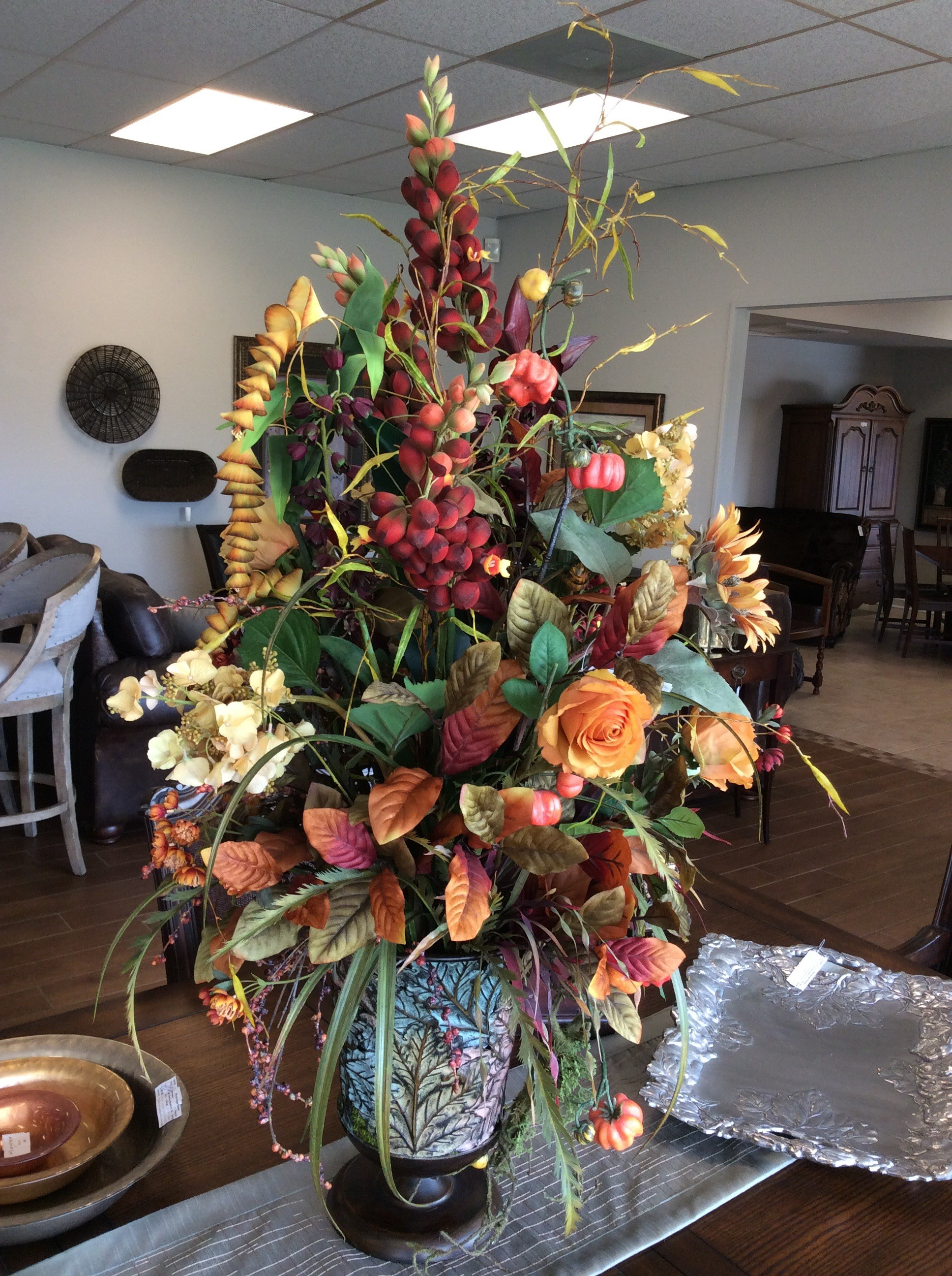 "This fall floral belongs on your Harvest/Thanksgiving table! It is large, stands 48"" high and 30"" across. Replete with all the colors of autumn, it features pumpkins, roses, sunflowers, berries and vines, oh my! Sitting in a lovely metal planter. it's perfect!"