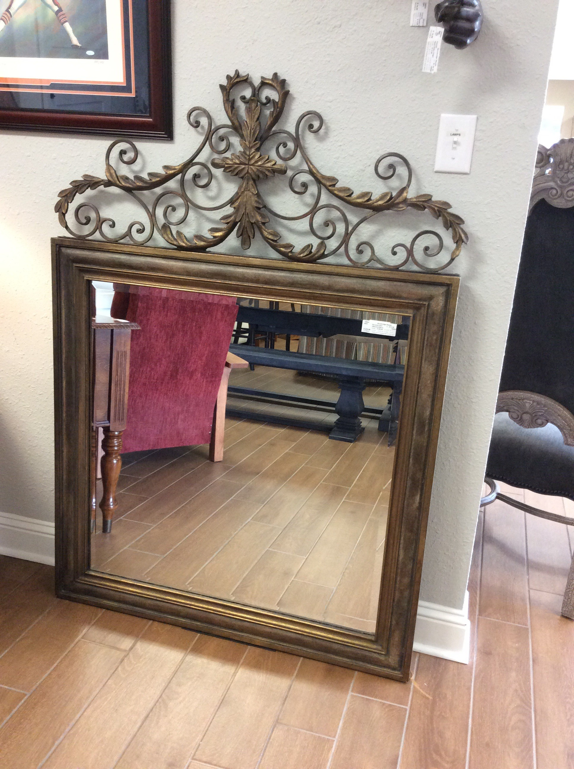 "This ornate mirror by Uttermost is lovely. Large at 42"" x 60"",  the top is adorned by scrollwork and vines giving it a vintagy, antiqued look."