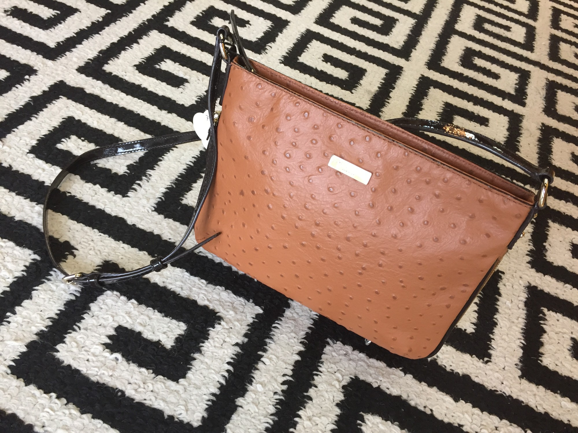 Brand New Kate Spade crossbody with dark caramel ostrich leather trimmed in dark chocolate patent leather. Has purse width extender with gold hardware. Interior lining is 100% polyester and there is no sign of use. This bag is in PERFECT condition. Retail: $299