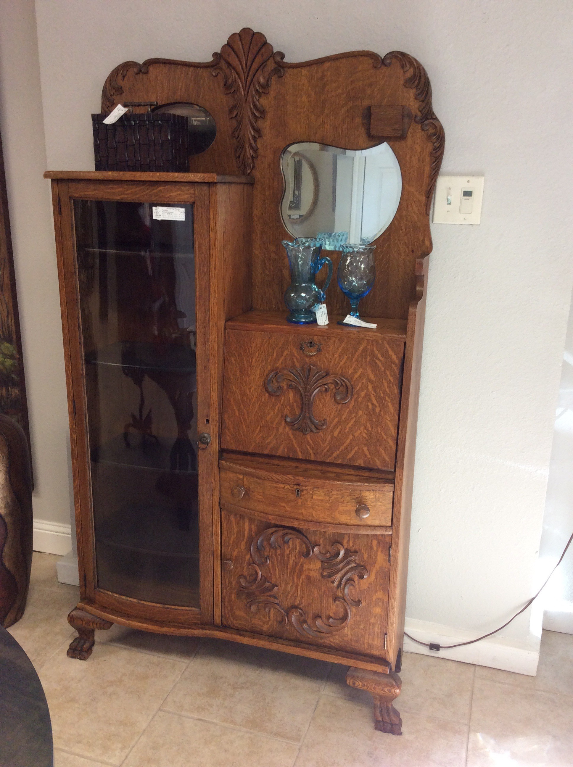 This is a lovely old piece!  It doubles as both a curio cabinet and a secretary desk. The curio has 4 adjustable shelves. The secretary features a drawer, a lovely carved wood cabinet on the bottom, and the desk top has several cubbies and a tiny drawer. The top has 2 mirrors and there is a key.