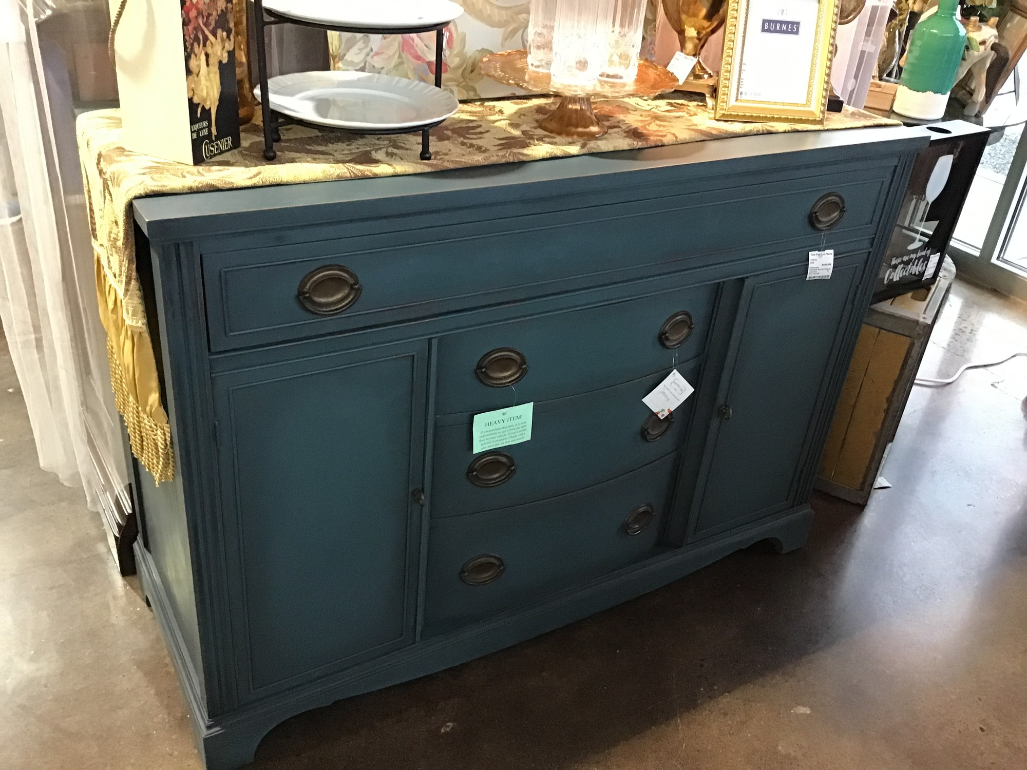 "This beautifully painted cabinet by one of our local artists was painted using Country Chic's Jitterbug paint (teal) and then distressed and waxed. It is perfect as a server in your dining room or kitchen, media stand, hallway piece or bedroom cabinet. Great statement piece in any room!<br /> Dimensions are 50-1/2"" x 19"" x 36"""