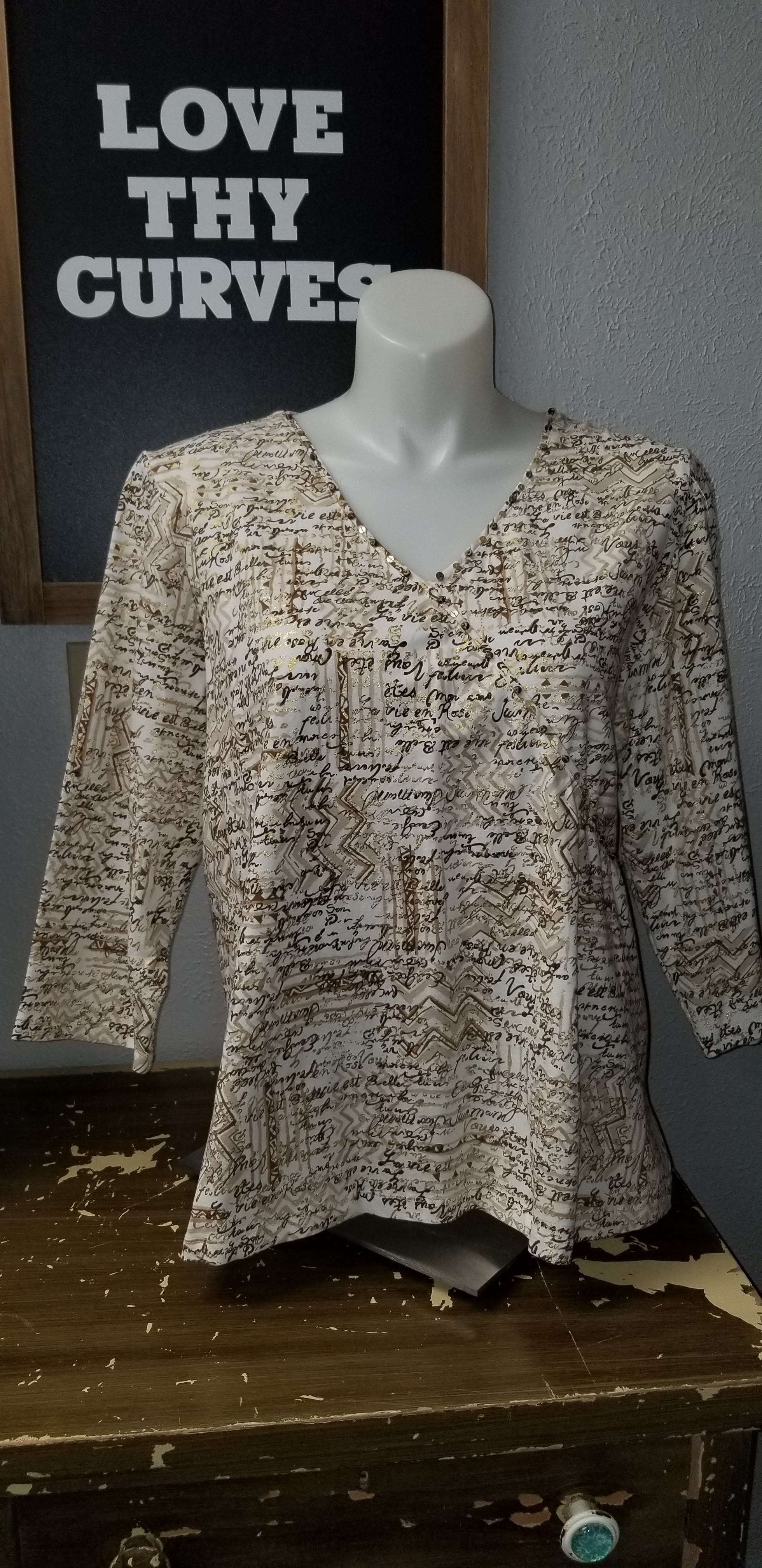 3/4 sleeve knit top with script style design, some gold metallic bling. Great Top!