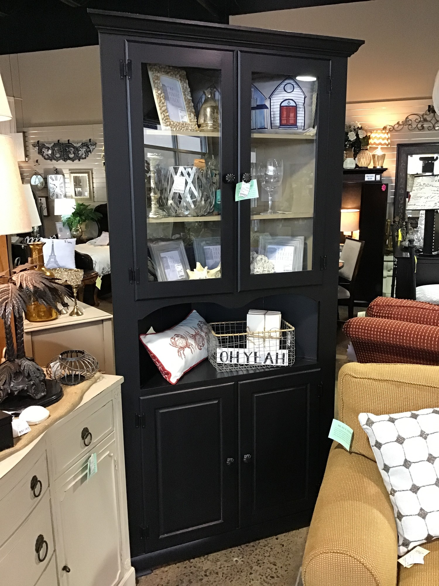 "Add storage space and style to your home with this lovely display stand. Crafted from pine wood, it showcases a classic frame with molded details and panel accents. This stand features two two-door cabinets, one with glass panels and one with wood panels,for all your storage needs.  This has been painted black but the inside of the glass doors has been painted tan.<br /> <br /> Dimensions:  28"" x 18"" x 82"""