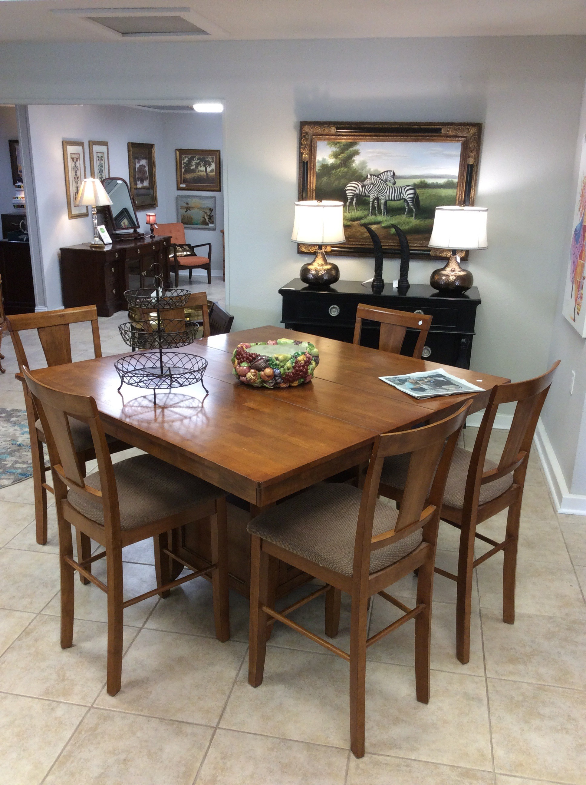"BARGAIN ALERT!!! This dining set is quite versatile. The table is in good condition and has a self-contained 12"" butterfly leaf, that when in use, makes the table a 54"" square. It also has a shelf and a cabinet in the table base. The 6 chairs feature a neutral taupe colored upholstery that is also in good condition. Priced to move at only $495!!"