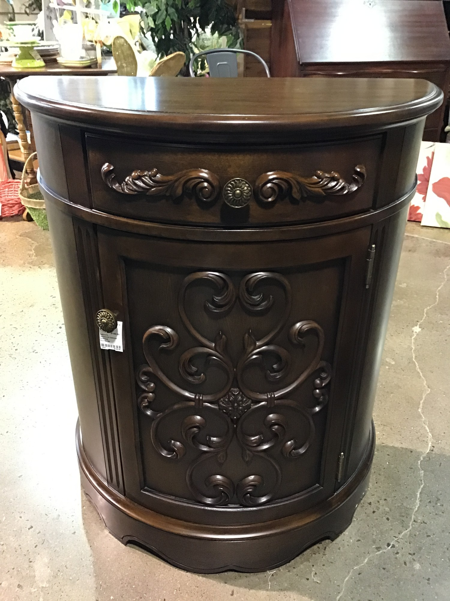 "This dark wood demilune cabinet has 1 cabinet door for storage and a small drawer. It has some pretty details that add interest to the piece.<br /> Dimensions are 30"" x 15"" x 36"""