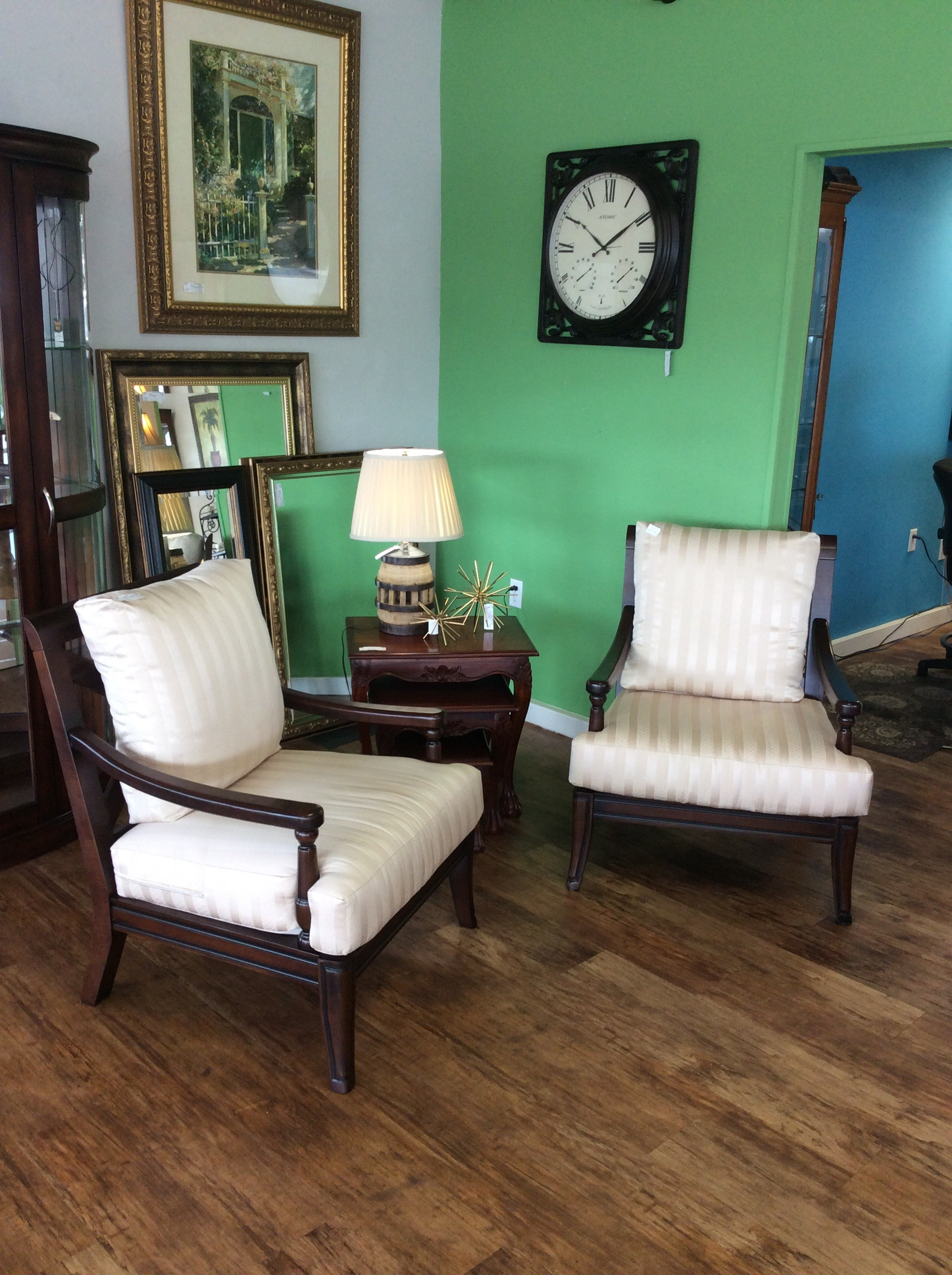 This comfy and oversized pair of armchairs are lovely! They feature a dark wood finish and are upholstered in a soft, cream colored stripe that adds a touch of glamour.