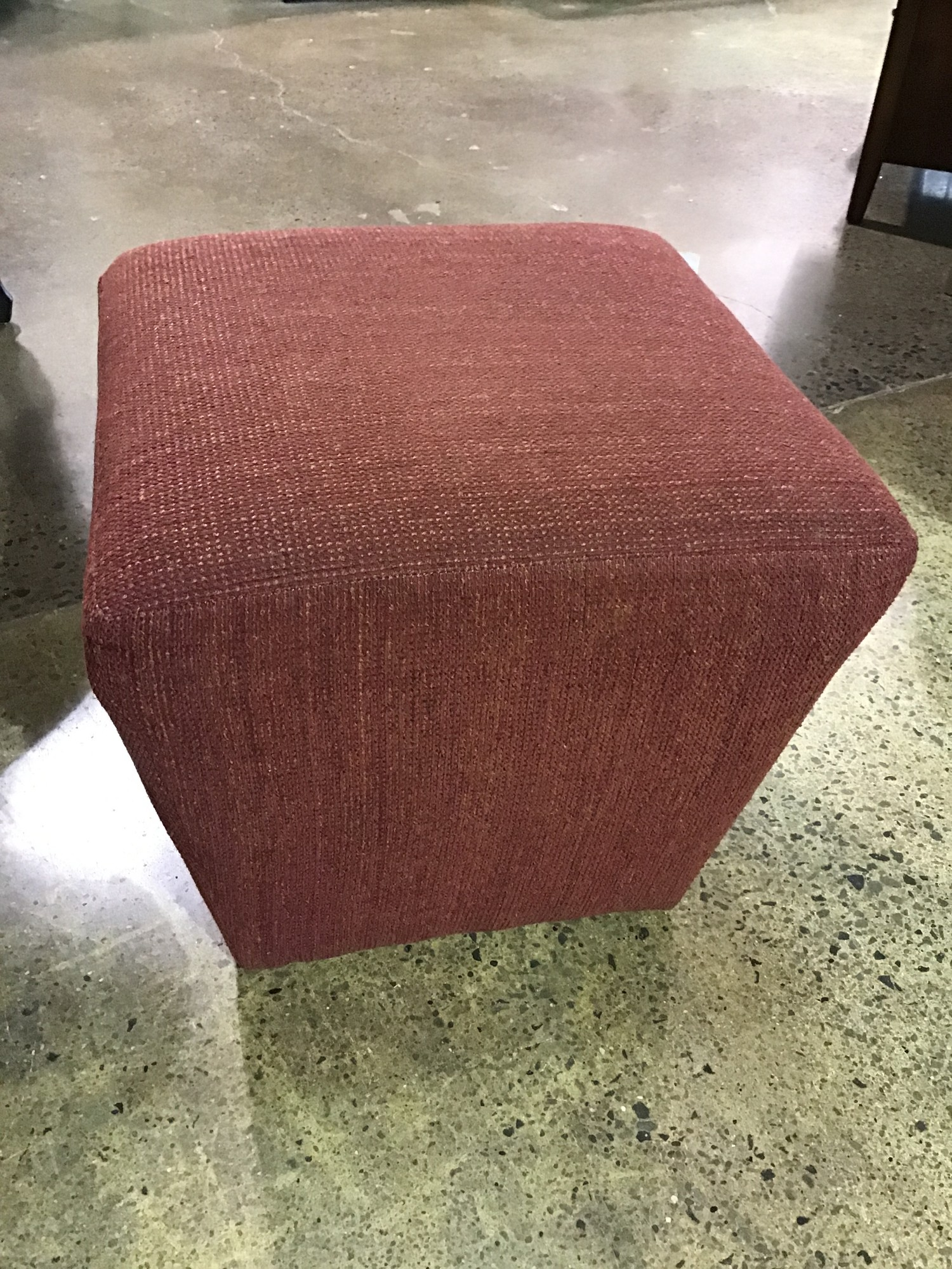 "This rust-colored cube ottoman is upholstered in a sturdy tweed fabric. Perfect ottoman for your favorite chair or to be used as extra seating. We have 2 of these which could be combined to form an upholstered coffee table!<br /> Dimensions are 18"" x 18"" x 19"""