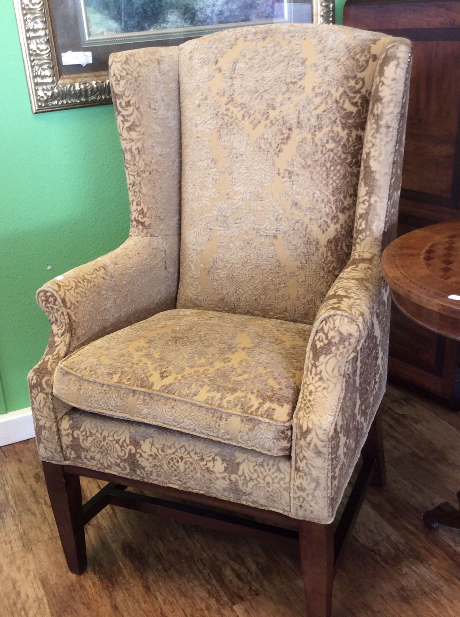 Warm the look of any room with a wingback chair from The Martha Stewart Signature Collection by Bernhardt Furniture. Traditional in style, it features a 2-toned gold Damask upholstery with a nailhead trim. Good condition.