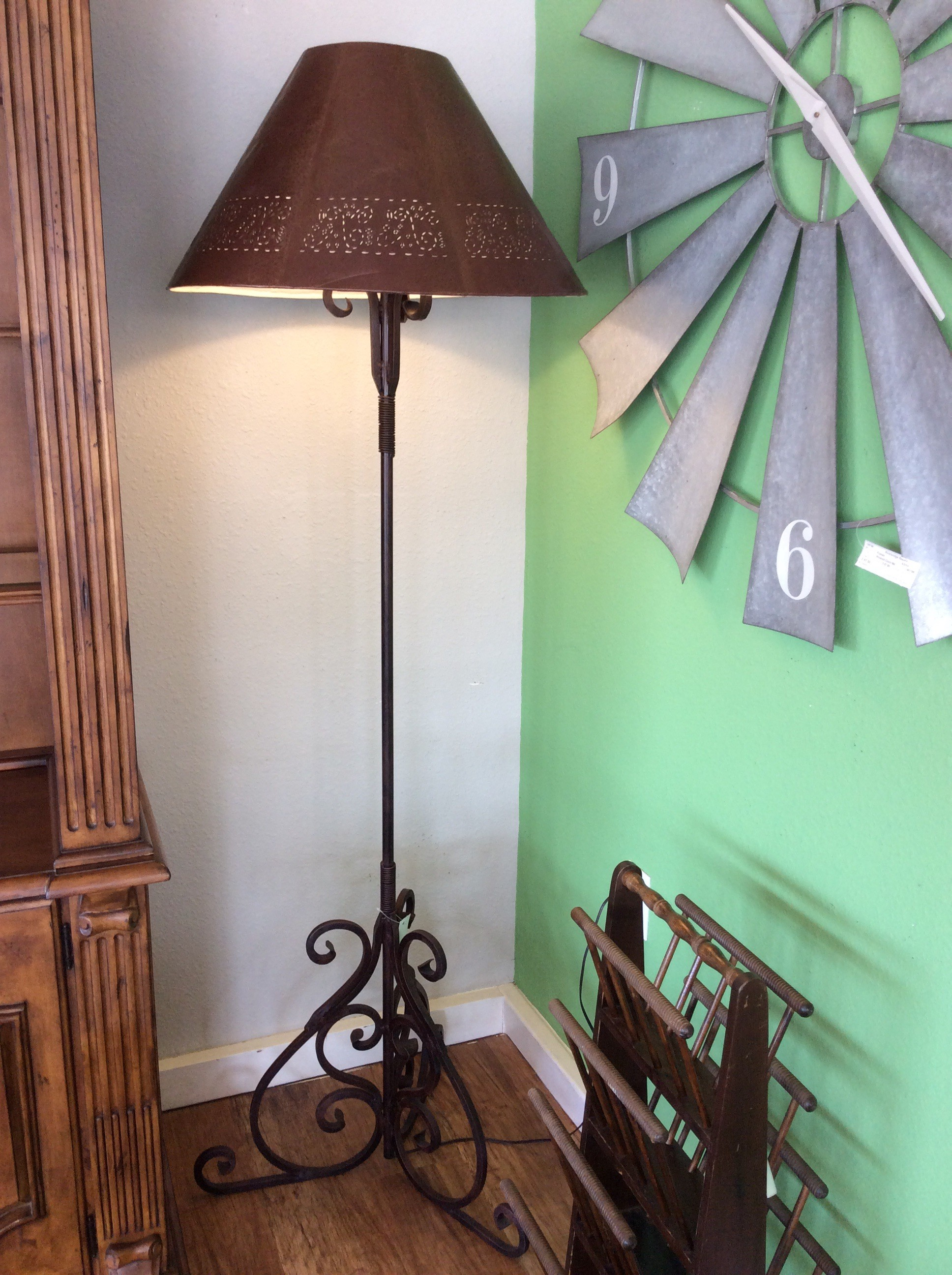 This is a charming floor lamp! Tall and slender, the painted iron base features lovely curvy scrollwork. The shade is an attractive contrast, kind of folkloreish or rustic in style.