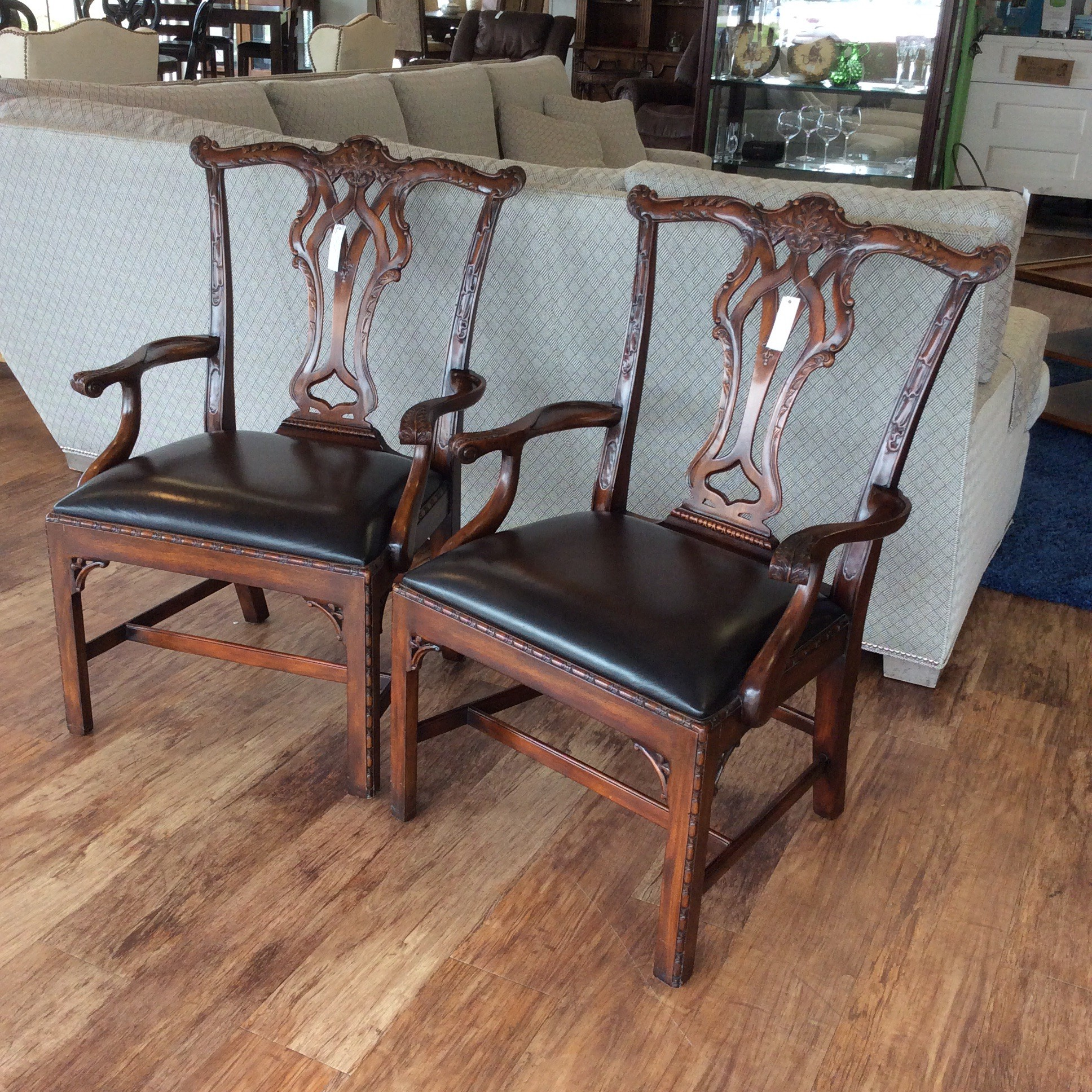 This is a stunning pair of chairs by Theo Alexander! Shaped by an historic English heiritage, this is one of the finest luxury brands in the world! This pair must be seen to be appreciated. They feature solid wood construction, a rich, dark wood finish, gorgeous ornate and detailed woodwork and fine leather upholstery. They represent an attention to detail and pride in quality craftsmanship that is hard to find these days.